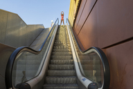 Young sportive woman on escalator - AFVF01329
