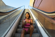 young woman sitting on escalator, using smartphone - AFVF01335