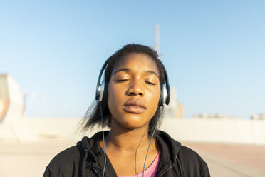 Young sportive woman listening music with headphones, eyes closed - AFVF01344