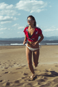 Portrait of laughing teenage girl running on the beach - ACPF00158