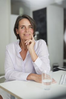 Portrait of pensive mature businesswoman sitting at desk - PNEF00845