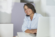 Portrait of smiling mature businesswoman in an office - PNEF00848