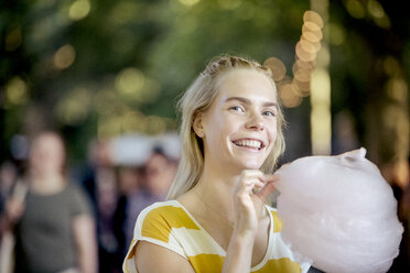Portrait of happy young woman with candy floss on streetfood festival - JESF00001