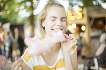 Portrait of young woman eating pink candy floss on streetfood festival - JESF00007