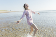 Netherlands, young woman in water at the beach in summer - JESF00010