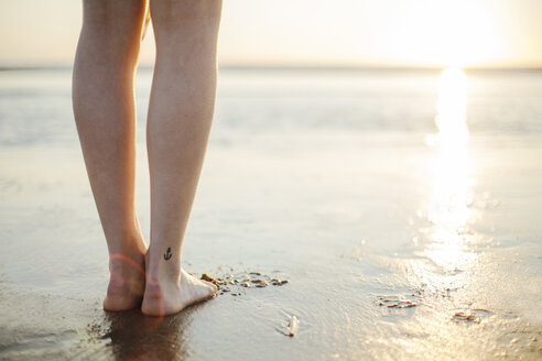 Young woman with tattoo anchor on ankle standing on beach at sunset - JESF00013