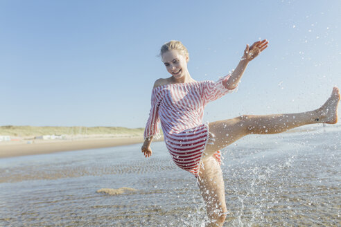 Netherlands, young woman splashing water at the beach in summer - JESF00016