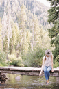 Woman sitting on a wooden bridge over a stream. - MINF06034