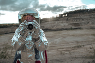 Spaceman on nameless planet taking pictures with camera - VPIF00473