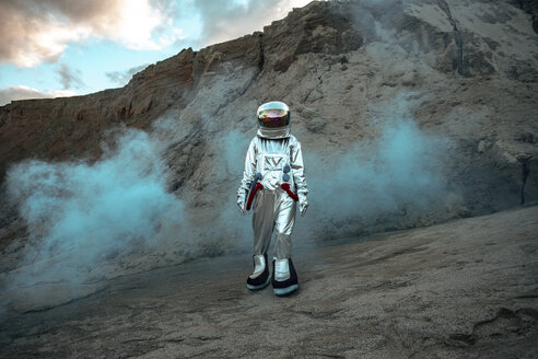 Spaceman exploring nameless planet, walking in a dust cloud - VPIF00476