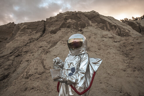 Spaceman on nameless planet taking samples of sand - VPIF00494