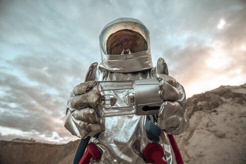 Spaceman exploring nameless planet, holding analyzer - VPIF00497
