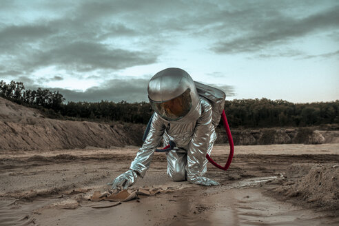 Spaceman exploring nameless planet, searching the soil - VPIF00506