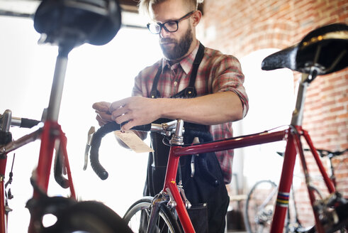 A man working in a bicycle repair shop. - MINF06282