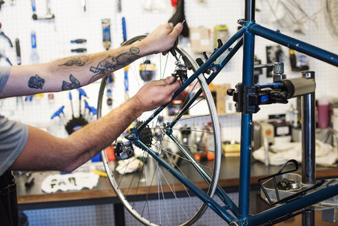 A man working in a bicycle repair shop. - MINF06297