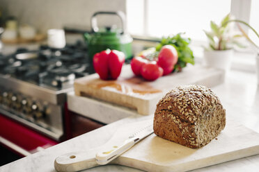 A fresh loaf of baked brown bread on a board with a breadknife. - MINF06333
