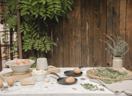 A table in a garden, fresh eggs in a bowl and two omelette pans. - MINF06447