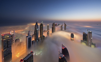 View of illuminated skyscrapers above the clouds in Dubai, United Arab Emirates at dusk. - MINF06513