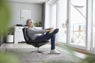 Mature man relaxing on leather chair in his living room looking out of window - RBF06473
