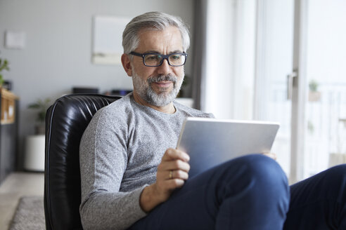 Portrait of mature man using tablet at home - RBF06476