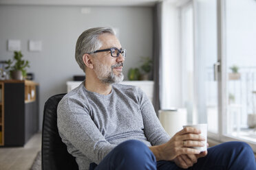 Content mature man relaxing with cup of coffee at home - RBF06479