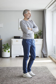 Mature man standing in his living room looking out of window - RBF06482