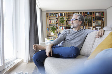 Mature man relaxing on couch in his living room looking out of window - RBF06485