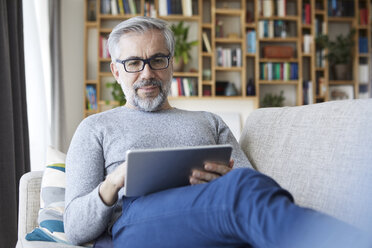 Portrait of mature man sitting on couch at his living room using tablet - RBF06488