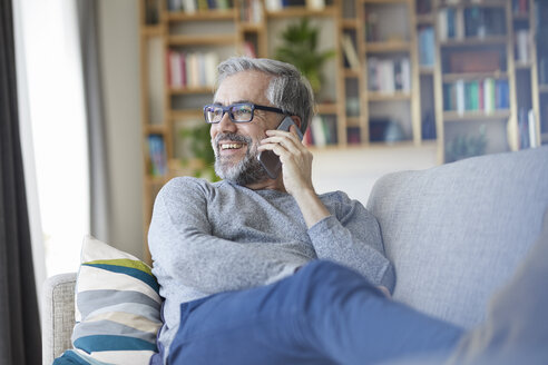 Mature man on the phone sitting on couch at home looking out of window - RBF06491