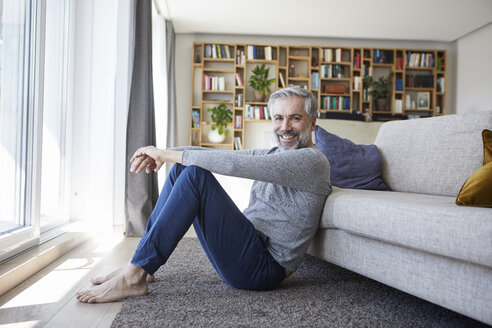 Portrait of happy mature man sitting on floor of his living room - RBF06494