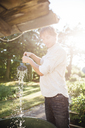 Man with watering can in garden - JESF00022