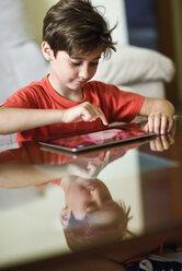 Portrait of little girl using digital tablet at home - JSMF00391