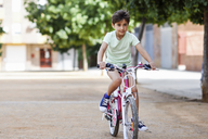 Portrait of little girl riding bicycle - JSMF00394