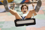 Portrait of screaming little girl having fun on a swing - JSMF00400