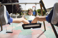 Portrait of smiling little girl having fun on a swing - JSMF00403
