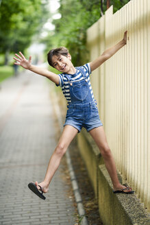 Portrait of laughing little girl playing outdoors - JSMF00412