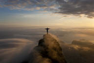 High angle view of colossal Christ Redeemer statue surrounded by clouds at dusk, Corcovado, Rio de Janeiro, Brazil. - MINF06548