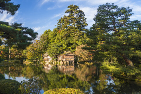 Landscape garden in autumn, with trees and pond, a boathouse in the distance. - MINF06587