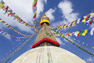 Low angle view of colourful prayer flags on stupa of Buddhist temple. - MINF06596