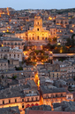 High angle view over illuminated rooftops of traditional houses in a Mediterranean city at dusk, church in the centre. - MINF06602