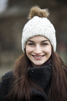 Portrait of smiling young woman wearing bobble hat - JESF00031
