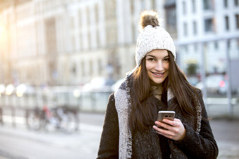 Portrait of smiling young woman with cell phone in winter - JESF00049