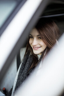 Portrait of smiling young woman driving car in winter - JESF00052