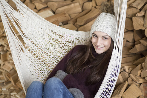 Portrait of smiling young woman wearing bobble hat and gloves sitting on hammock - JESF00055