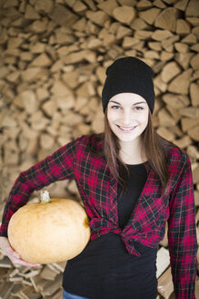 Portrait of smiling young woman with pumpkin - JESF00058