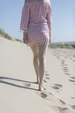 Young woman wearing short summer dress at the beach, walking - JESF00064