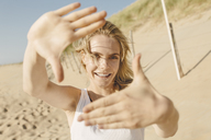 Portrait of young blond woman at the beach, shaping frame with her hands - JESF00070