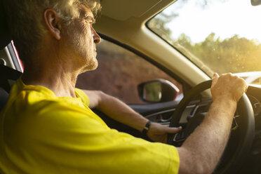 Senior man driving a car during sunset - AFVF01353