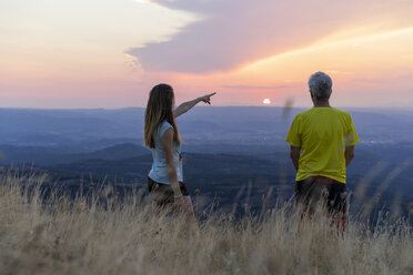 Spain, Catalonia, Montcau, senior father and adult daughter looking at view from top of hill during sunset - AFVF01359