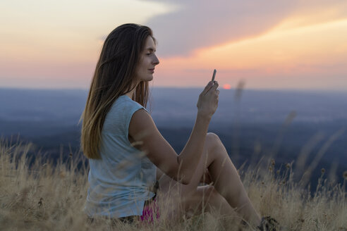 Spain, Catalonia, Montcau, young woman using cell phone sitting in grass on top of hill during sunset - AFVF01362